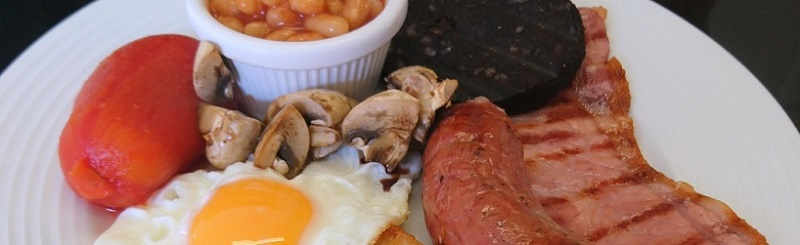 Picture of a full english breakfast, beans, sausages, bacon, mushrooms, egg