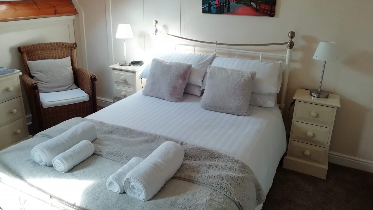 Photograph of Room 7 standard double bed with seating area with guest information booklets