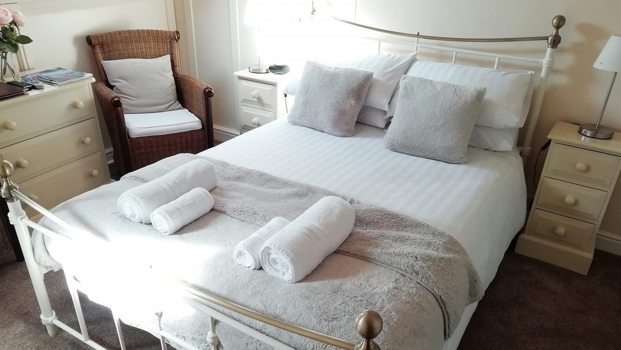 Photograph of Room 7 standard double bed with fluffy white towels