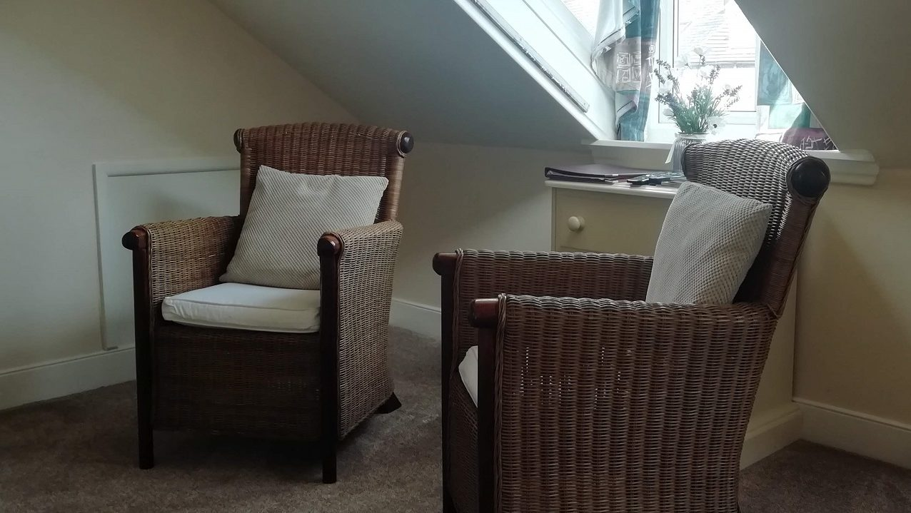 Photograph of Room 8 standard double bed with seating area with guest information booklets