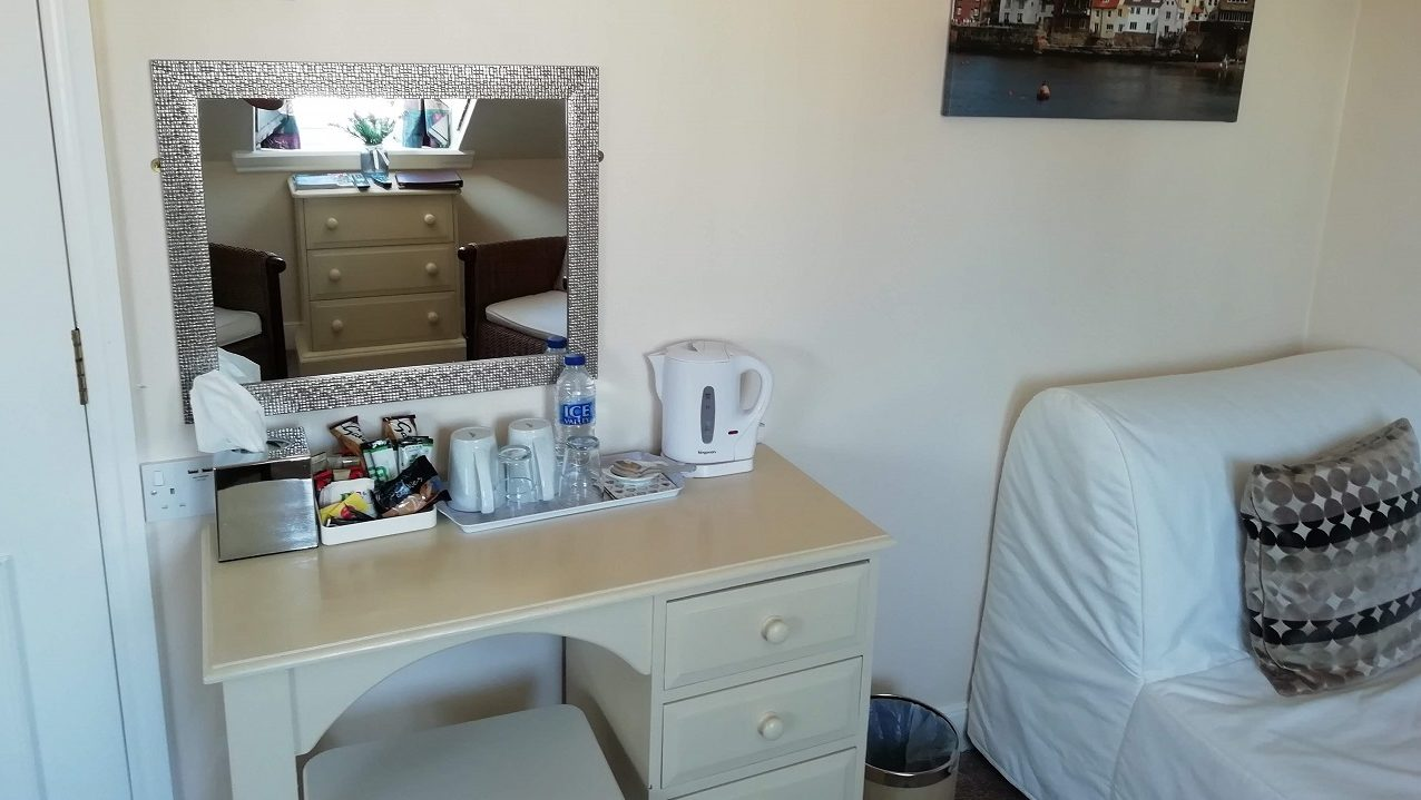 Photograph of Room 8 standard double bed with vanity yable, mirror and hospitality tray