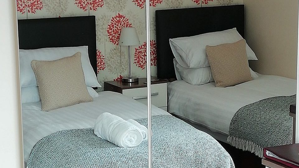 Photograph of Room 4 set up as a twin room - 2 beds through the mirrored wardrobe doors